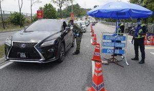 Polisi Malaysia memeriksa kendaraan di tengah pengendalian pergerakan di Kuala Lumpur untuk membatasi penyebaran virus Corona (AP Photo/Vincent Thian)